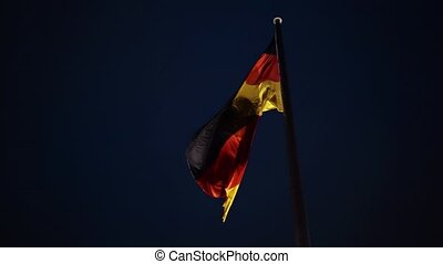 German national flag waving against a night sky background....