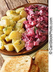 German red herring salad served with boiled potatoes closeup in a plate. vertical