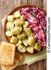 German red herring salad served with boiled potatoes closeup in a plate. Vertical top view