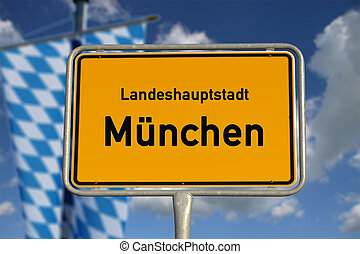 German road sign Munich, Bavaria with flag, blue sky and white clouds