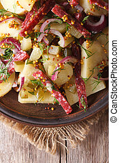 German salad of potatoes with salami and spices closeup vertical