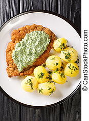 German schnitzel with boiled potatoes and Frankfurt green sauce close-up in a plate. vertical top view