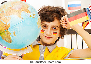 German schoolboy studying geography with a globe