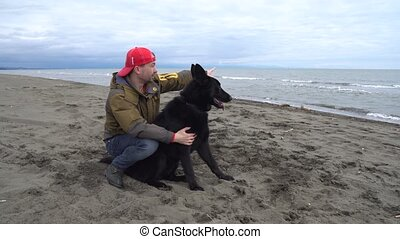 German Shepherd and its owner walk along shore of Black Sea...