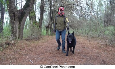 German Shepherd and its owner walk in the park, Poti
