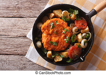 German Weiner schnitzel with vegetables in a pan. horizontal...