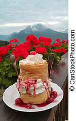 German Windbeutel (Cream Puffs) behind of red flowers over...