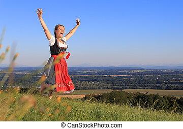 German Woman in Bavarian Dirndl jumping on the meadow