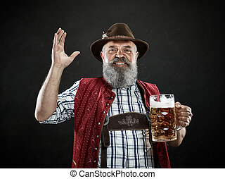 Germany, Bavaria, Upper Bavaria, man with beer dressed in in traditional Austrian or Bavarian costume