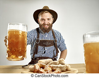 Germany, Bavaria, Upper Bavaria, man with beer dressed in traditional Austrian or Bavarian costume