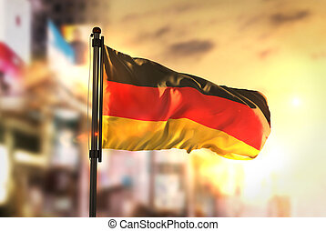 Germany Flag Against City Blurred Background At Sunrise Backlight