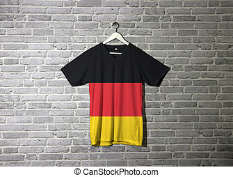 Germany flag on shirt and hanging on the wall with brick pattern wallpaper.