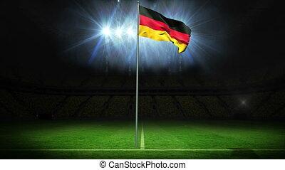 Germany national flag waving on flagpole against football...