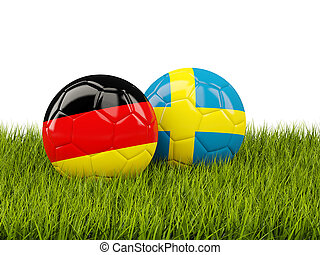 Germany vs Sweden. Soccer concept. Footballs with flags on green grass