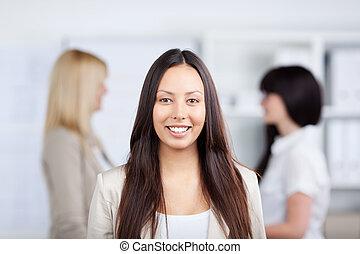 geschäftsfrau, lächeln, mit, weibliche , mitarbeiter, in, hintergrund
