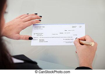 geschäftsfrau, unterzeichnender scheck