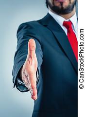 Geschäftsmann gibt die Hand zur Begrüßung