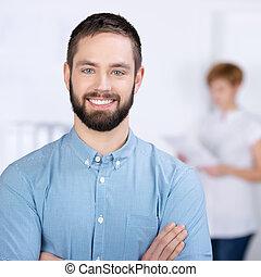 geschäftsmann, lächeln, mit, weibliche , mitarbeiter, in, hintergrund