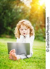geshockeerde, en, vrolijke , verwonderd, kind, met, draagbare computer, zittende , op, de, gra