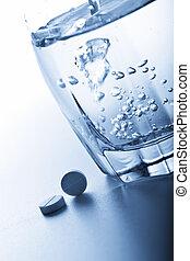 gestemd blauw, waterglas, pillen, aspirine