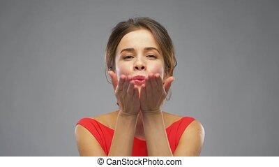 beautiful woman in red sending air kiss - gesture and...