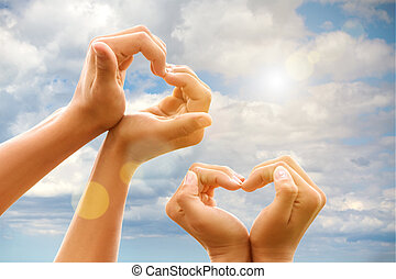 gesture hands heart of on backdrop of the sky