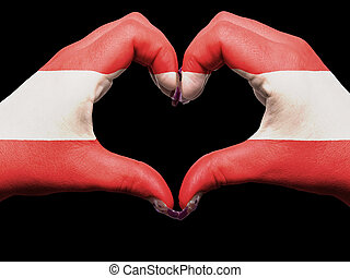 Gesture made by austria flag colored hands showing symbol of heart and love