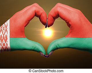 Gesture made by belarus flag colored hands showing symbol of heart and love during sunrise