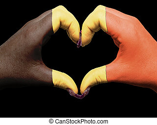 Gesture made by belgium flag colored hands showing symbol of heart and love