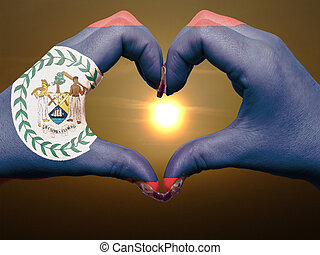 Gesture made by belize flag colored hands showing symbol of heart and love during sunrise