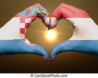 Gesture made by croatia flag colored hands showing symbol of heart and love during sunrise