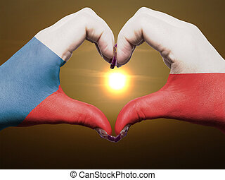 Gesture made by czech flag colored hands showing symbol of heart and love during sunrise