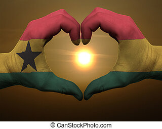 Gesture made by ghana flag colored hands showing symbol of heart and love during sunrise