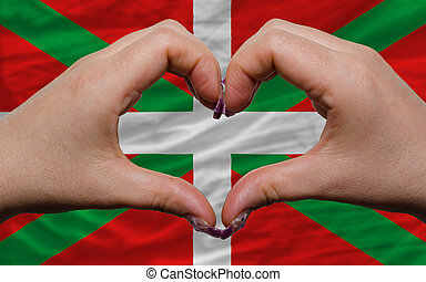 Gesture made by hands showing symbol of heart and love over flag of basque