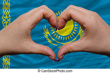 Gesture made by hands showing symbol of heart and love over national kazakhstan flag