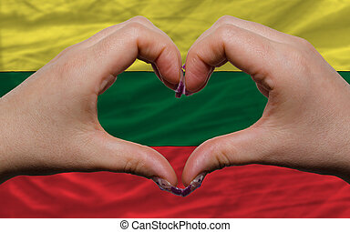 Gesture made by hands showing symbol of heart and love over national lithuania flag