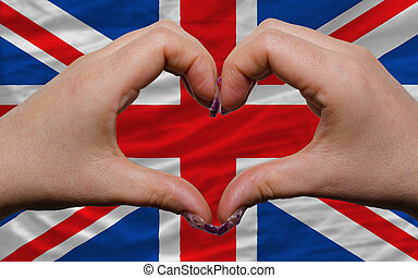 Gesture made by hands showing symbol of heart and love over national united kingdom flag