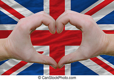 Gesture made by hands showing symbol of heart and love over united kingdom flag