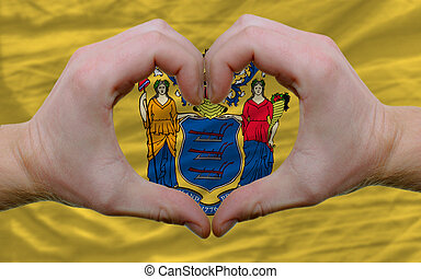 Gesture made by hands showing symbol of heart and love over us state flag of new jersey