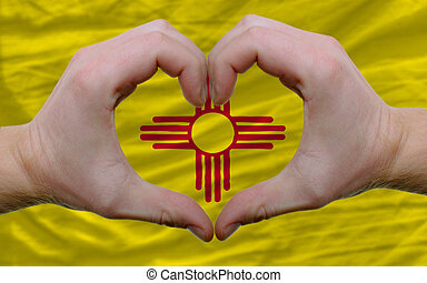 Gesture made by hands showing symbol of heart and love over us state flag of new mexico