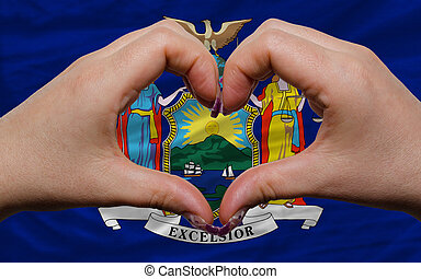 Gesture made by hands showing symbol of heart and love over us state flag of new york