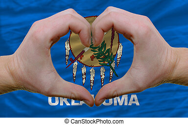 Gesture made by hands showing symbol of heart and love over us state flag of oklahoma