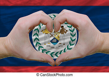 Gesture made by hands showing symbol of heart and love over belize flag