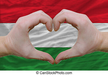 Gesture made by hands showing symbol of heart and love over hungary flag