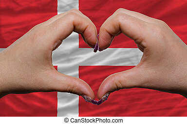 Gesture made by hands showing symbol of heart and love over national denmark flag