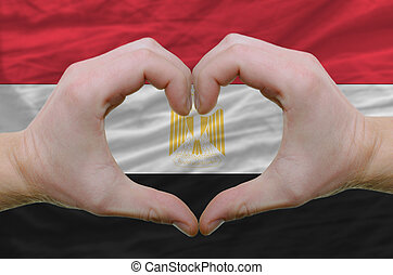 Gesture made by hands showing symbol of heart and love over egypt flag