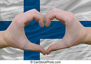 Gesture made by hands showing symbol of heart and love over finland flag
