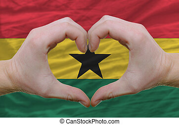 Gesture made by hands showing symbol of heart and love over ghana flag