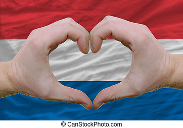 Gesture made by hands showing symbol of heart and love over holland flag