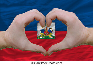 Gesture made by hands showing symbol of heart and love over haiti flag